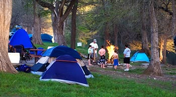 Families enjoying group campfire outside of tents